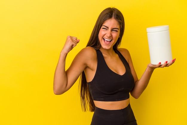 勝利、勝者の概念の後に拳を上げる黄色の背景に分離されたタンパク質ボトルを保持している若い白人女性。