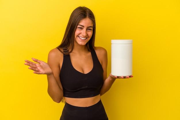 黄色の背景に分離されたタンパク質ボトルを保持している若い白人女性は、嬉しい驚きを受け取り、興奮し、手を上げます。