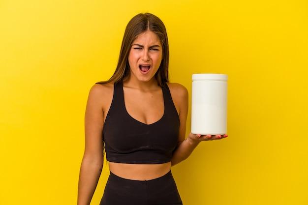 非常に怒って攻撃的な叫び声黄色の背景に分離されたタンパク質ボトルを保持している若い白人女性。