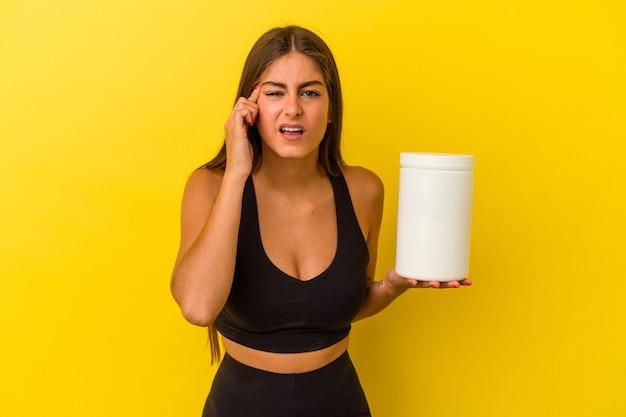 집게 손가락으로 실망 제스처를 보여주는 노란색 배경에 고립 된 단백질 병을 들고 젊은 백인 여자.