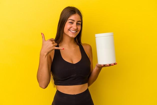 指で携帯電話の呼び出しジェスチャーを示す黄色の背景に分離されたタンパク質ボトルを保持している若い白人女性。