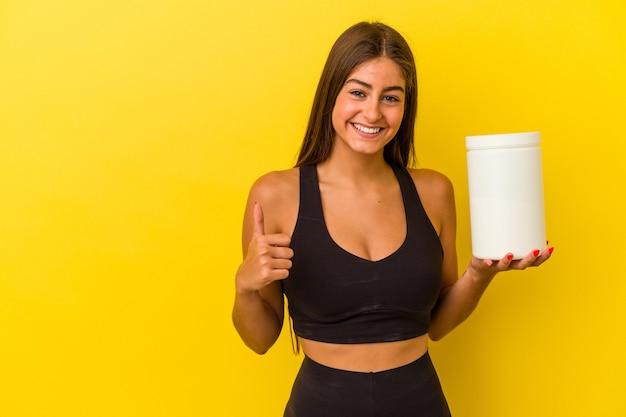笑顔と親指を上げて黄色の背景に分離されたタンパク質ボトルを保持している若い白人女性
