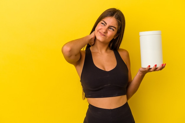頭の後ろに触れて、考えて選択を行う黄色の背景に分離されたタンパク質ボトルを保持している若い白人女性。