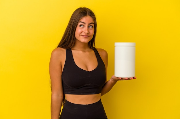 목표와 목적 달성을 꿈꾸는 노란색 벽에 고립 된 단백질 병을 들고 젊은 백인 여자