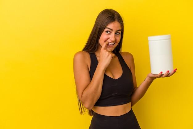 노란색 벽에 고립 된 단백질 병을 들고 젊은 백인 여자 복사본 공간을보고 뭔가에 대해 편안 하 게 생각.