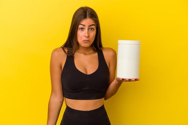 노란색 벽에 고립 된 단백질 병을 들고 젊은 백인 여자는 어깨를 으쓱 하 고 혼란 스 러 워 눈을 뜨고.