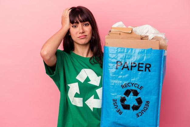 Молодая кавказская женщина, держащая переработанный картонный мешок на розовом фоне, была потрясена, она вспомнила важную встречу.