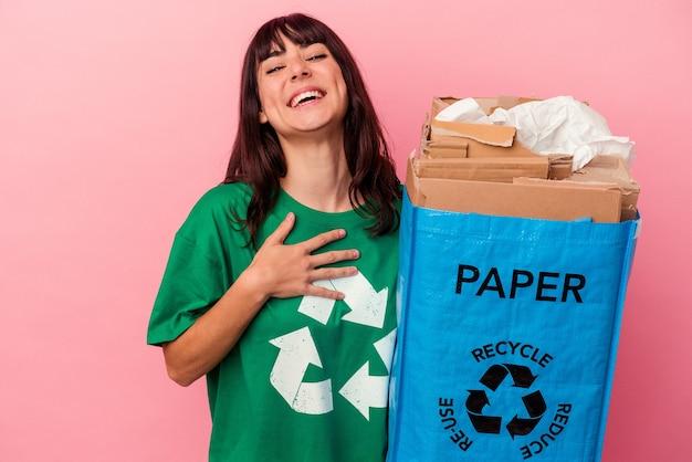 Молодая кавказская женщина, держащая переработанный картонный мешок, изолированный на розовой стене, громко смеется, держа руку на груди.
