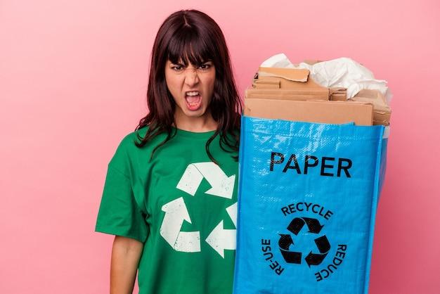 Молодая кавказская женщина, держащая переработанный картонный пакет, изолирована на розовой стене, кричит очень сердито и агрессивно