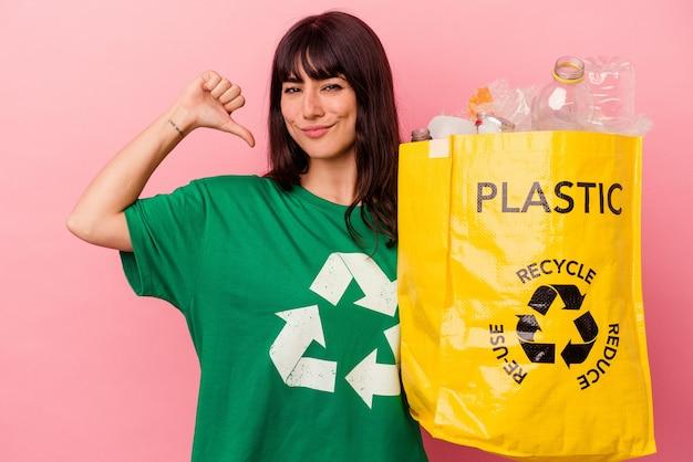 분홍색 배경에 고립 된 재활용 비닐 봉지를 들고 젊은 백인 여자는 자랑스럽고 자신감을 느낍니다.