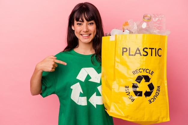 자부심과 자신감, 셔츠 복사 공간을 손으로 가리키는 분홍색 배경 사람에 고립 된 재활용 비닐 봉지를 들고 젊은 백인 여자