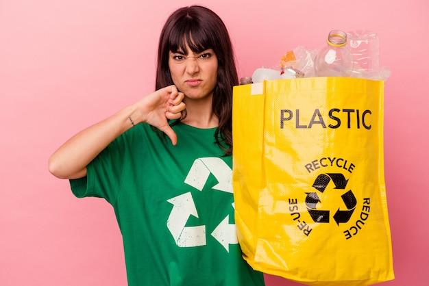젊은 백인 여자 싫어하는 제스처를 보여주는 분홍색 배경에 고립 된 재활용 된 비닐 봉지를 들고 아래로 엄지 손가락. 불일치 개념.
