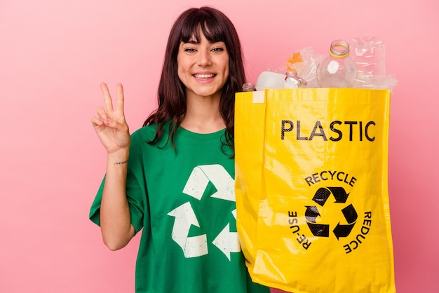 젊은 백인 여자는 손가락으로 2 번을 보여주는 분홍색 배경에 고립 된 재활용 된 비닐 봉지를 들고.
