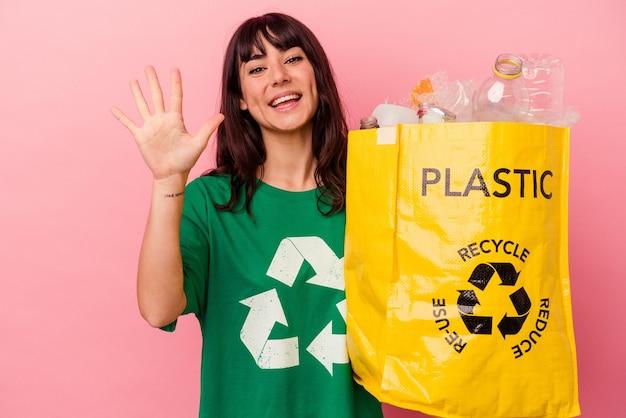 분홍색 배경에 고립 된 재활용 된 비닐 봉지를 들고 젊은 백인 여자 손가락으로 명랑 게재 번호 5 웃 고.