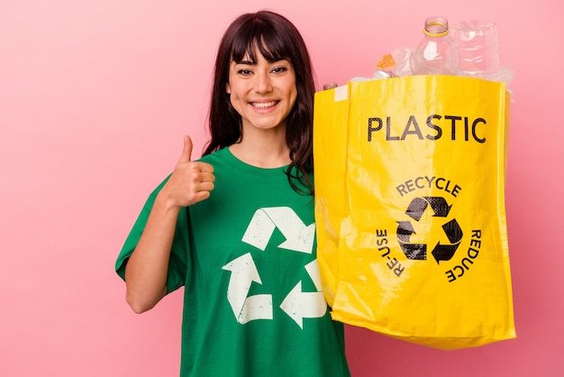 웃 고 엄지 손가락을 올리는 분홍색 벽에 고립 된 재활용 비닐 봉지를 들고 젊은 백인 여자