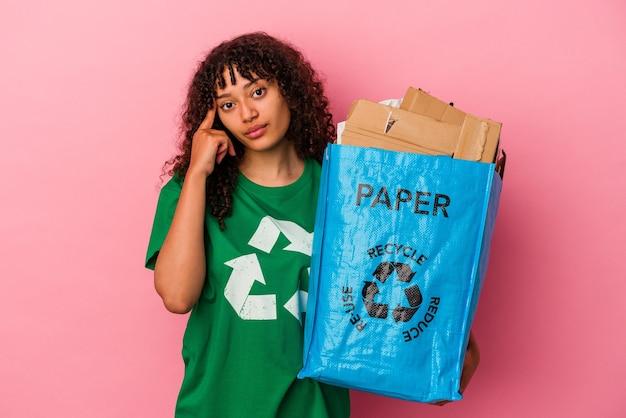 Молодая кавказская женщина, держащая переработанный пластик, изолирована на розовом фоне, указывая висок пальцем, думая, сосредоточилась на задаче.