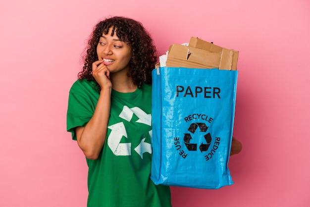 ピンクの背景に分離された再生プラスチックを保持している若い白人女性は、コピースペースを見ている何かについて考えてリラックスしました。