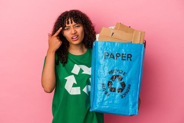 Молодая кавказская женщина, держащая переработанный пластик, изолированную на розовом фоне, показывает жест разочарования указательным пальцем.