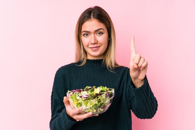 指でナンバーワンを示す孤立したサラダを保持している若い白人女性。