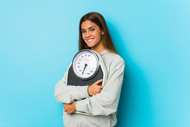 Молодая кавказская женщина, держащая весы, изолированные на синем фоне