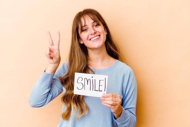 Молодая кавказская женщина, держащая изолированный плакат улыбки, показывающая номер два пальцами.