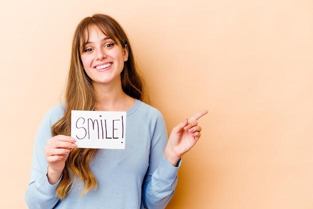 Молодая кавказская женщина, держащая плакат улыбки изолировала улыбаясь и указывая в сторону, показывая что-то на пустом месте.