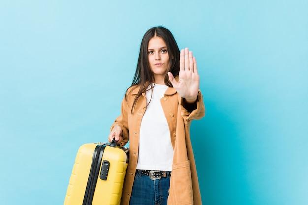 Молодая кавказская женщина, держащая чемодан, стоя с протянутой рукой, показывая знак остановки, предотвращая вас.