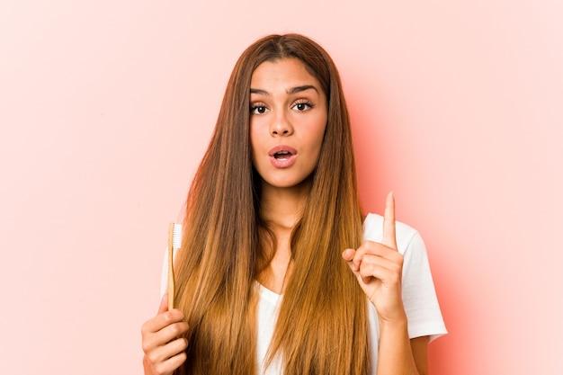 いくつかの素晴らしいアイデア、創造性の概念を持っている歯ブラシを持っている若い白人女性。