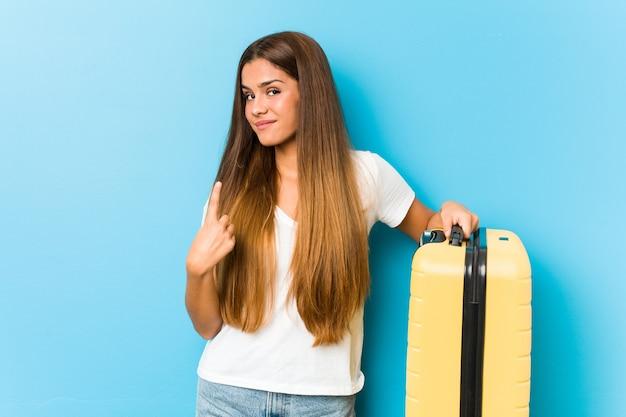 誘うように指で指さしている旅行スーツケースを持った若い白人女性が近づいてくる。