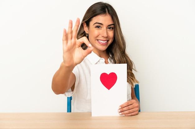 バレンタインデーカードを持っている若い白人女性は、大丈夫なジェスチャーを示す陽気で自信を持って孤立しました。