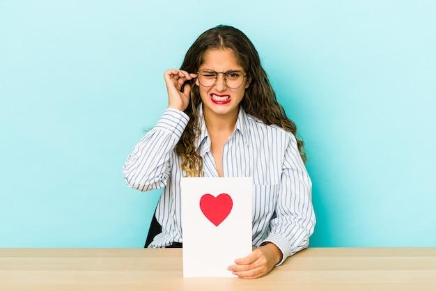 발렌타인 데이 카드를 들고 젊은 백인 여자는 손으로 귀를 덮고 격리.