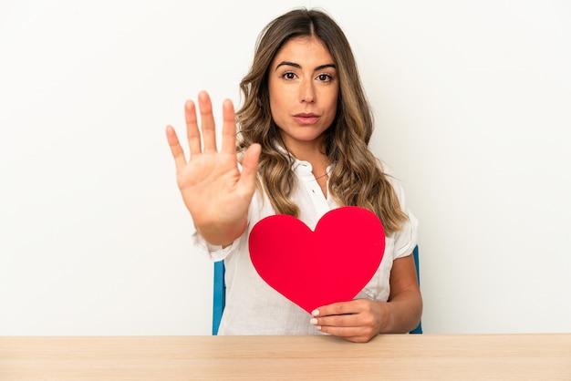 발렌타인 하트를 들고 젊은 백인 여자는 당신을 방지하는 정지 신호를 보여주는 뻗은 손으로 서 고립.