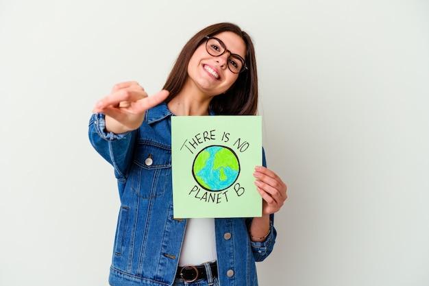 Молодая кавказская женщина держит плакат веганской жизни, изолированный на белой стене, указывая пальцем на вас, как будто приглашая подойти ближе.