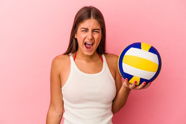 Молодая кавказская женщина, держащая волейбольный мяч на розовом фоне, кричала очень сердито и агрессивно.