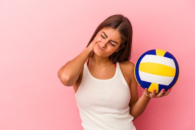 Молодая кавказская женщина держит волейбольный мяч на розовой стене, касаясь затылка, думая и делая выбор.