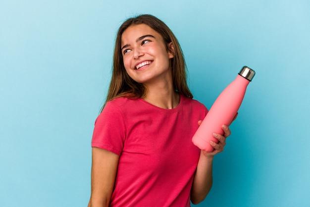 青い背景に分離された水のボトルを保持している若い白人女性は、笑顔、陽気で楽しい脇に見えます。