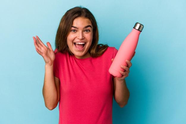 青い背景に分離された水のボトルを保持している若い白人女性は、嬉しい驚きを受け取り、興奮し、手を上げます。