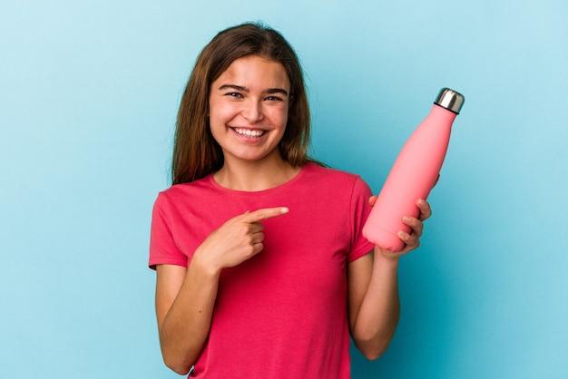 青い背景に分離された水のボトルを持って笑顔で脇を指して、空白のスペースで何かを示している若い白人女性。