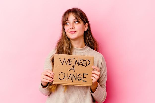Молодая кавказская женщина держит плакат с надписью we need a change, мечтающий о достижении целей и задач