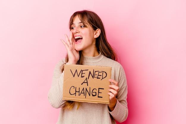 Молодая кавказская женщина, держащая мы нуждаемся в изолированном плакате изменения, кричащем и держа ладонь возле открытого рта.
