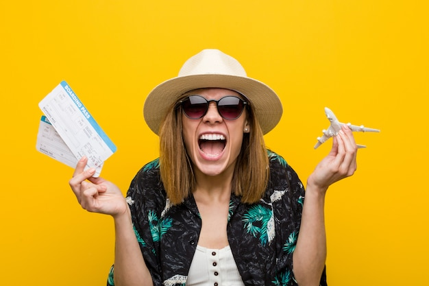 Young caucasian woman holding air tickets very happy.