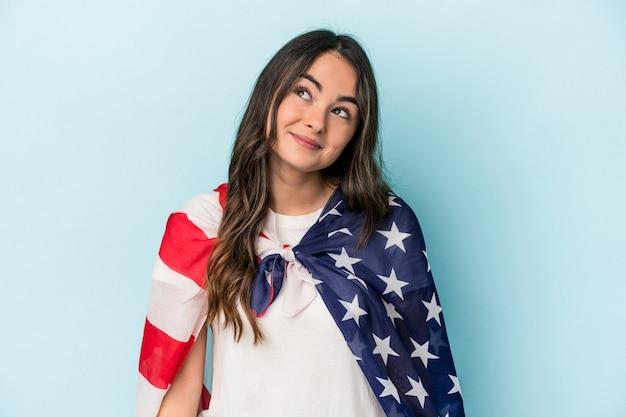 Молодая кавказская женщина, держащая американский флаг на синем фоне, мечтающая о достижении целей и задач