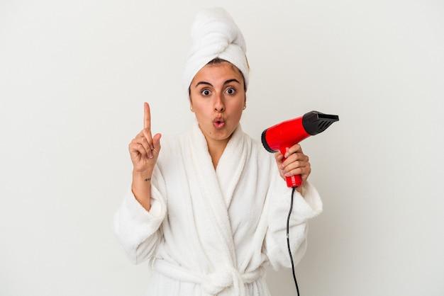 いくつかの素晴らしいアイデア、創造性の概念を持っている白で隔離されるヘアー ドライヤーを保持している若い白人女性。