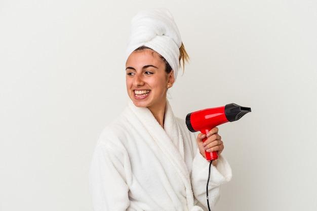 Молодая кавказская женщина, держащая фен для волос, изолированная на белом, смотрит в сторону, улыбаясь, веселая и приятная.
