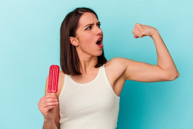 勝利、勝者の概念の後に拳を上げる青い背景で隔離のアイスクリームを保持している若い白人女性。