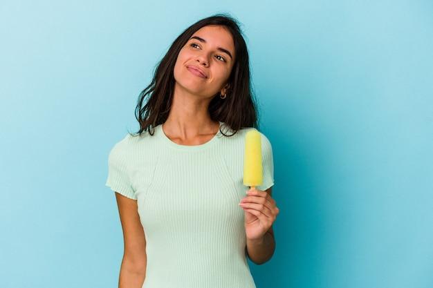 青い背景に分離されたアイスクリームを保持している若い白人女性目標と目的を達成することを夢見て青い背景に分離されたアイスクリームを保持している若い白人女性