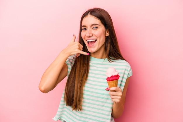 Молодая кавказская женщина, держащая мороженое, изолирована на розовом фоне, показывая жест мобильного телефона пальцами.
