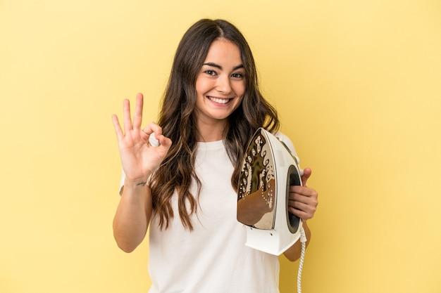 黄色の背景に分離された鉄を持っている若い白人女性は、陽気で自信を持って大丈夫なジェスチャーを示しています。