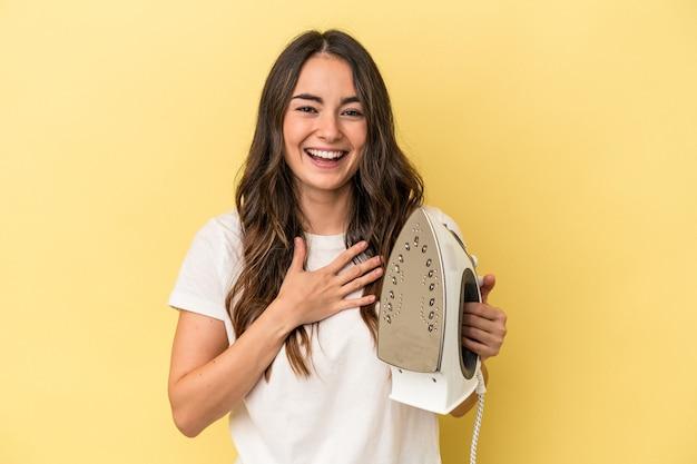 黄色の背景に分離された鉄を保持している若い白人女性は、胸に手を置いて大声で笑います。