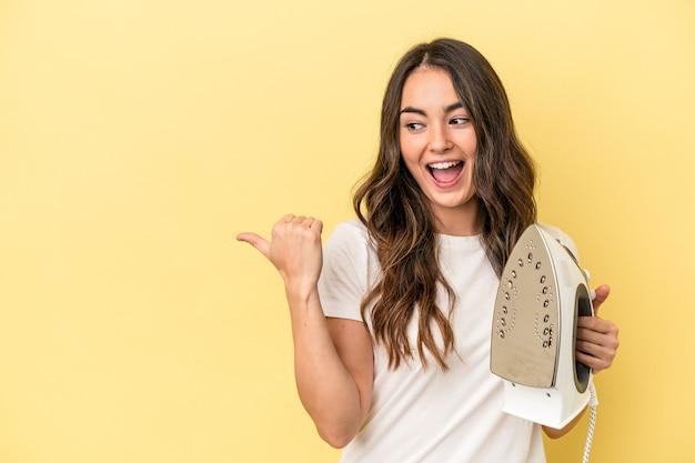 黄色の背景に分離された鉄を持っている若い白人女性は、親指の指を離れて、笑ってのんきなポイントを指します。